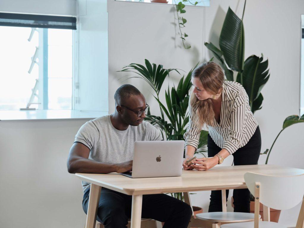 Zwei Mitarbeiter diskutieren über die Erstellung einer Reiserichtlinie