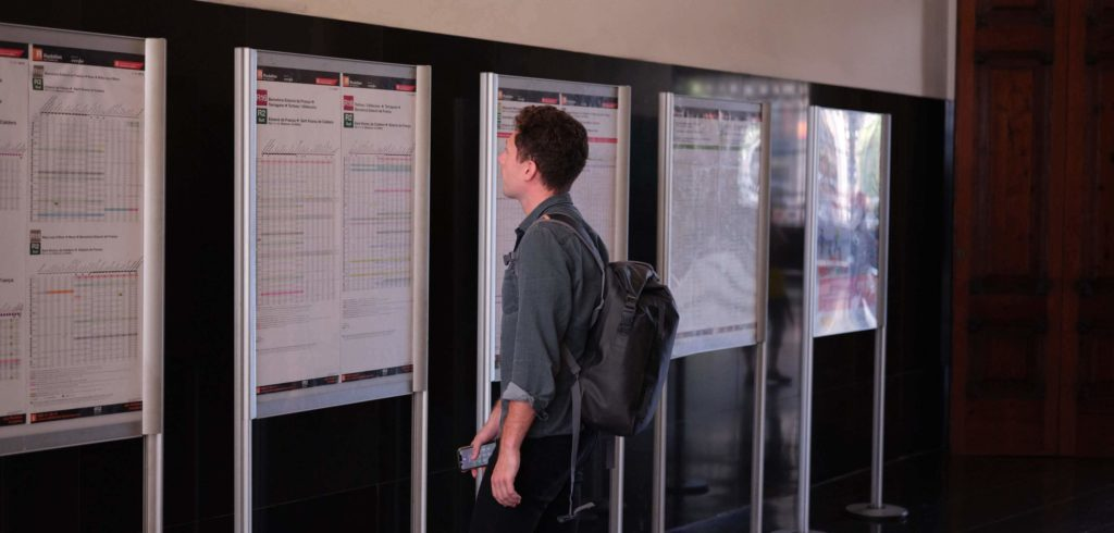 man looking at train times, header for coporate travel safety article