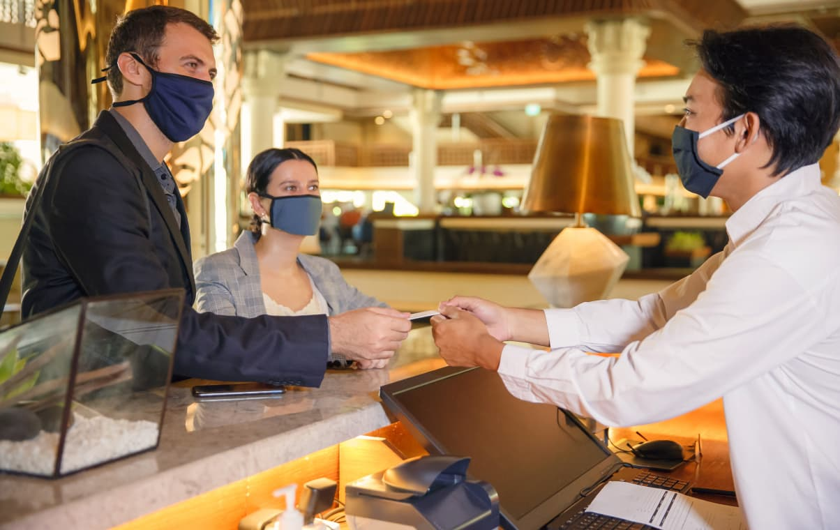 couple checking in a hotel with their face masks on